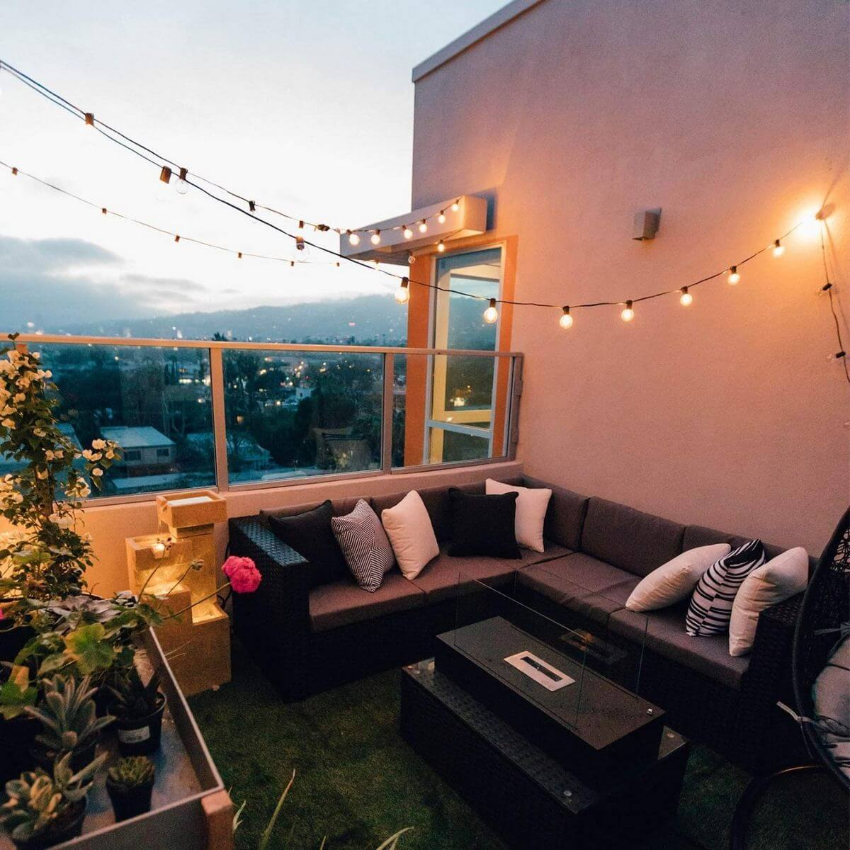 Balcony with string lights, a couch, and plants.