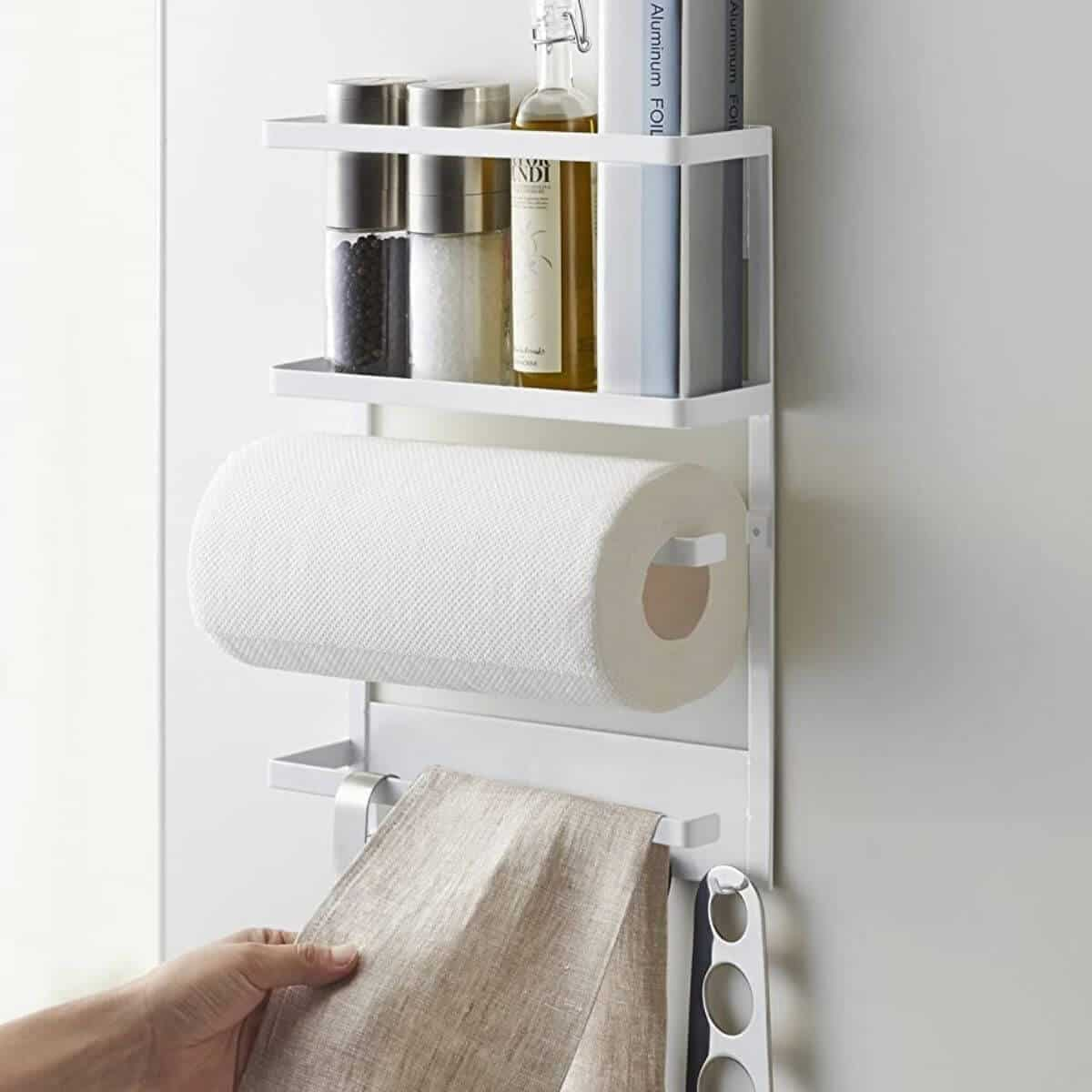 Magnetic storage rack holding kitchen items, paper towels, and a cloth.