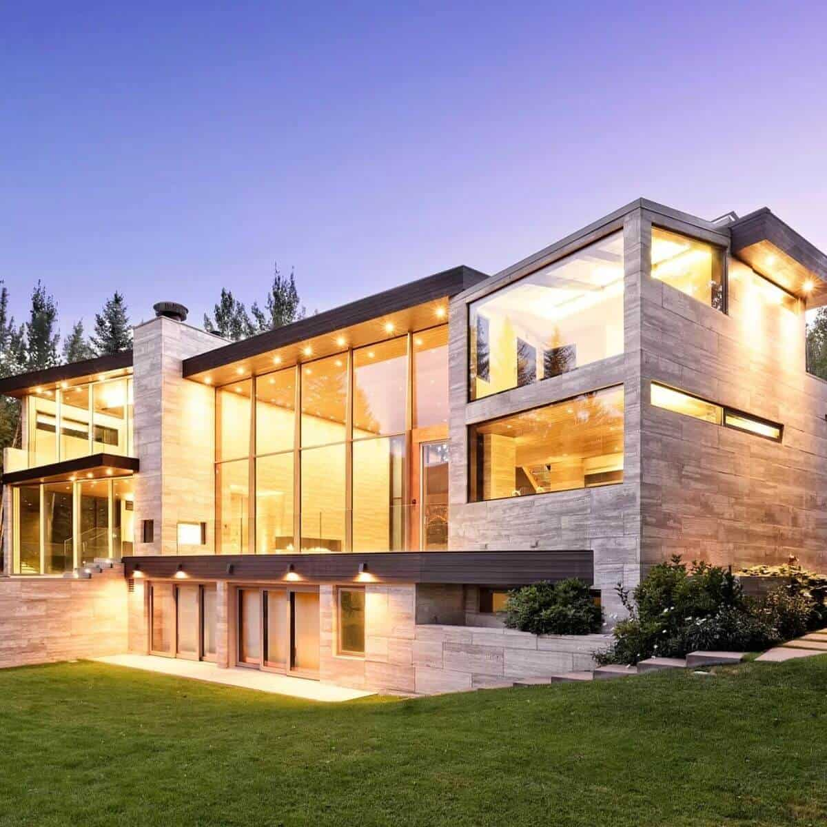 Modern 3-story mansion in Aspen with grass in front of it.