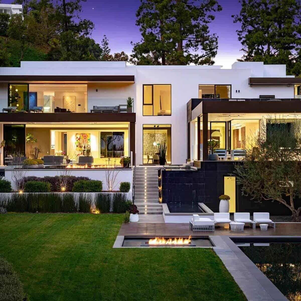 White and black modern mansion with a grass yard, fire pit, and pool.