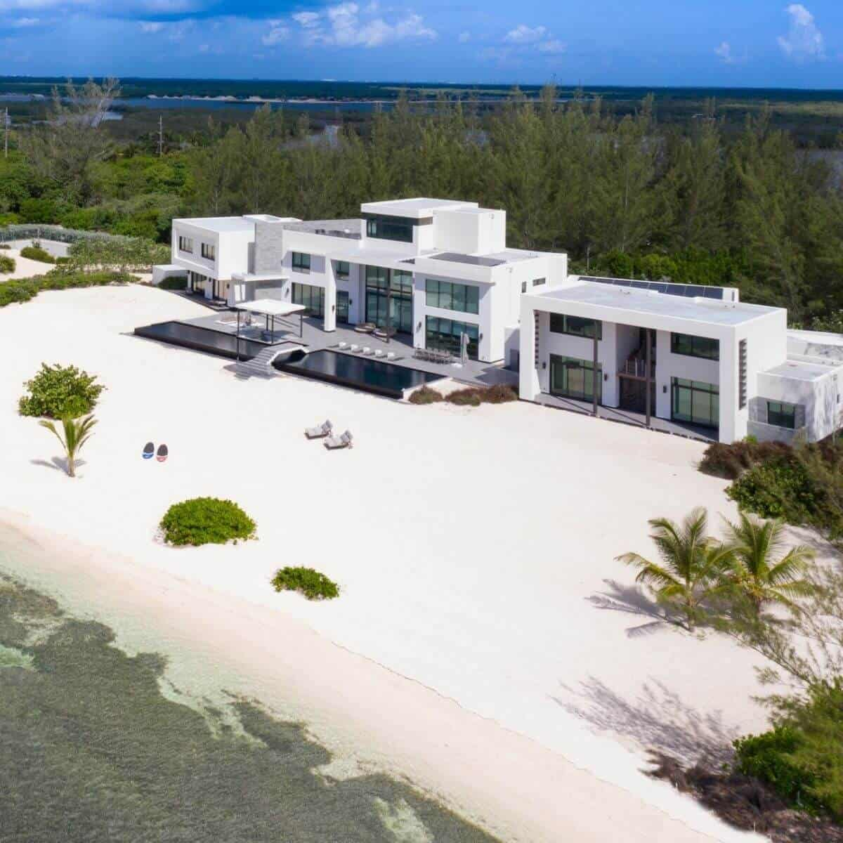 White 3-story modern mansion on a private white-sand beach with trees behind it.