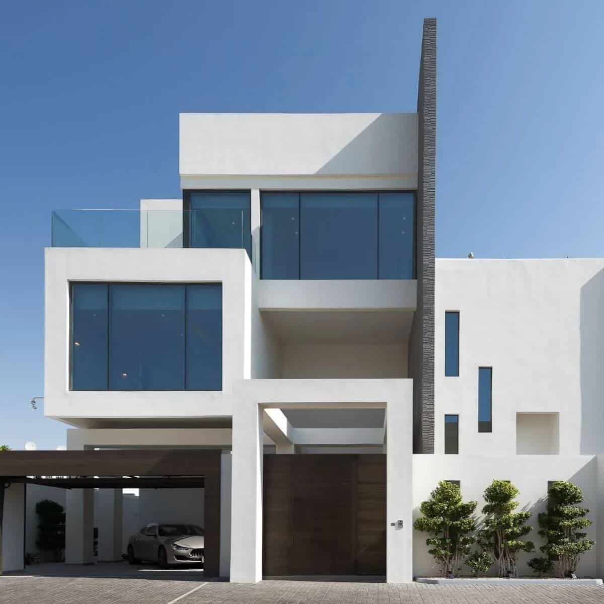 3-story white modern mansion with floor-to-ceiling windows and a car in the garage.