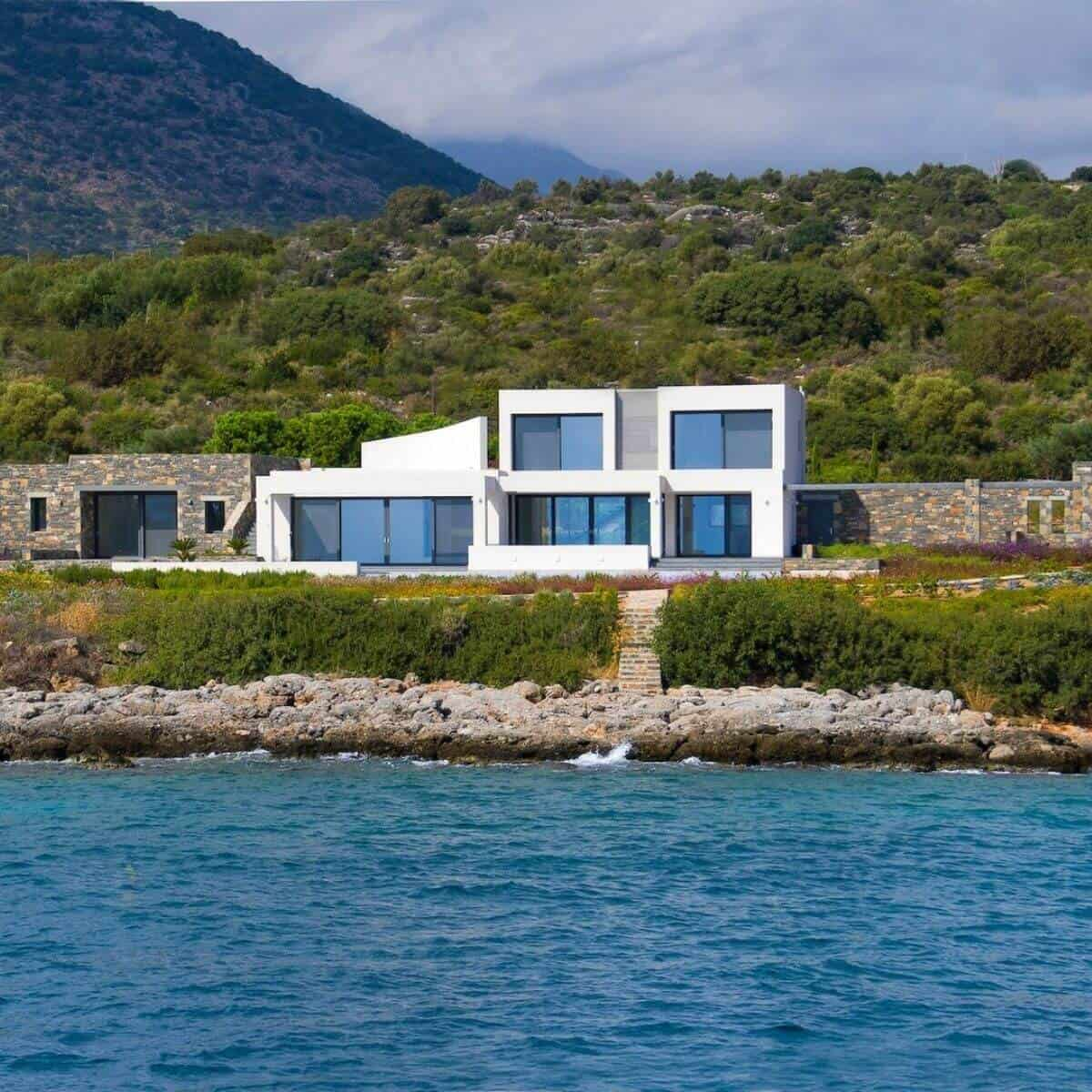 White and stone modern mansion next to the water and in front of hills and mountains.