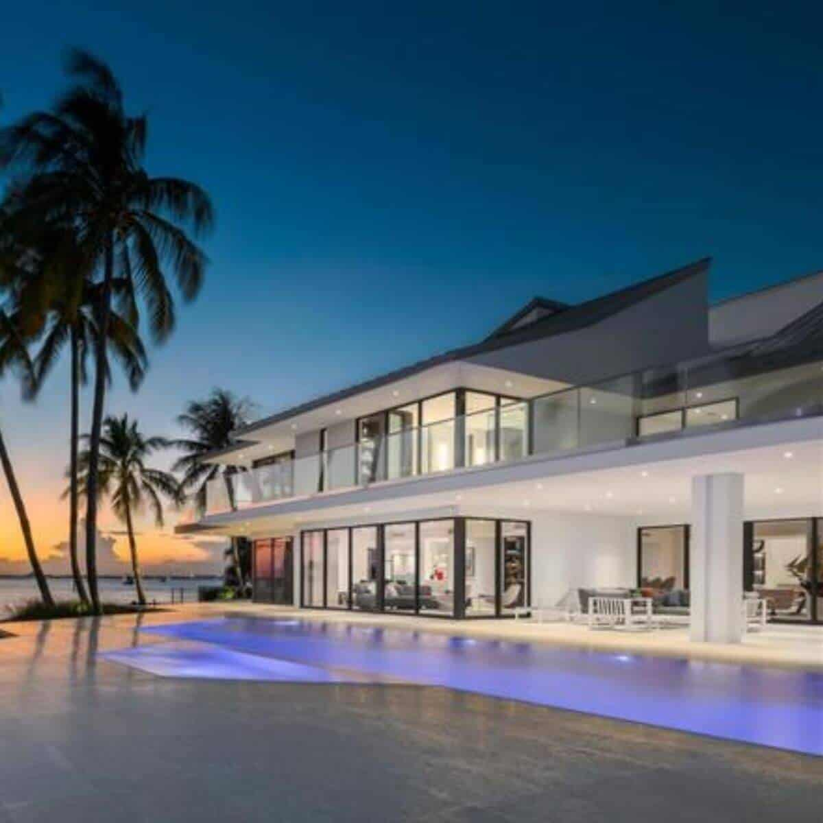 White 2-story modern mansion in Florida with a pool and view of the water during a sunset.