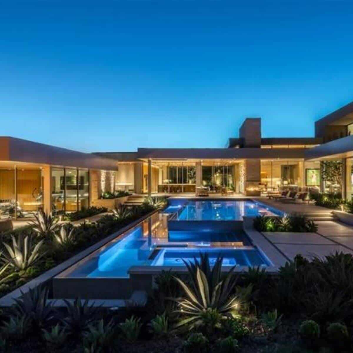 A pool in front of a modern mansion at dusk.