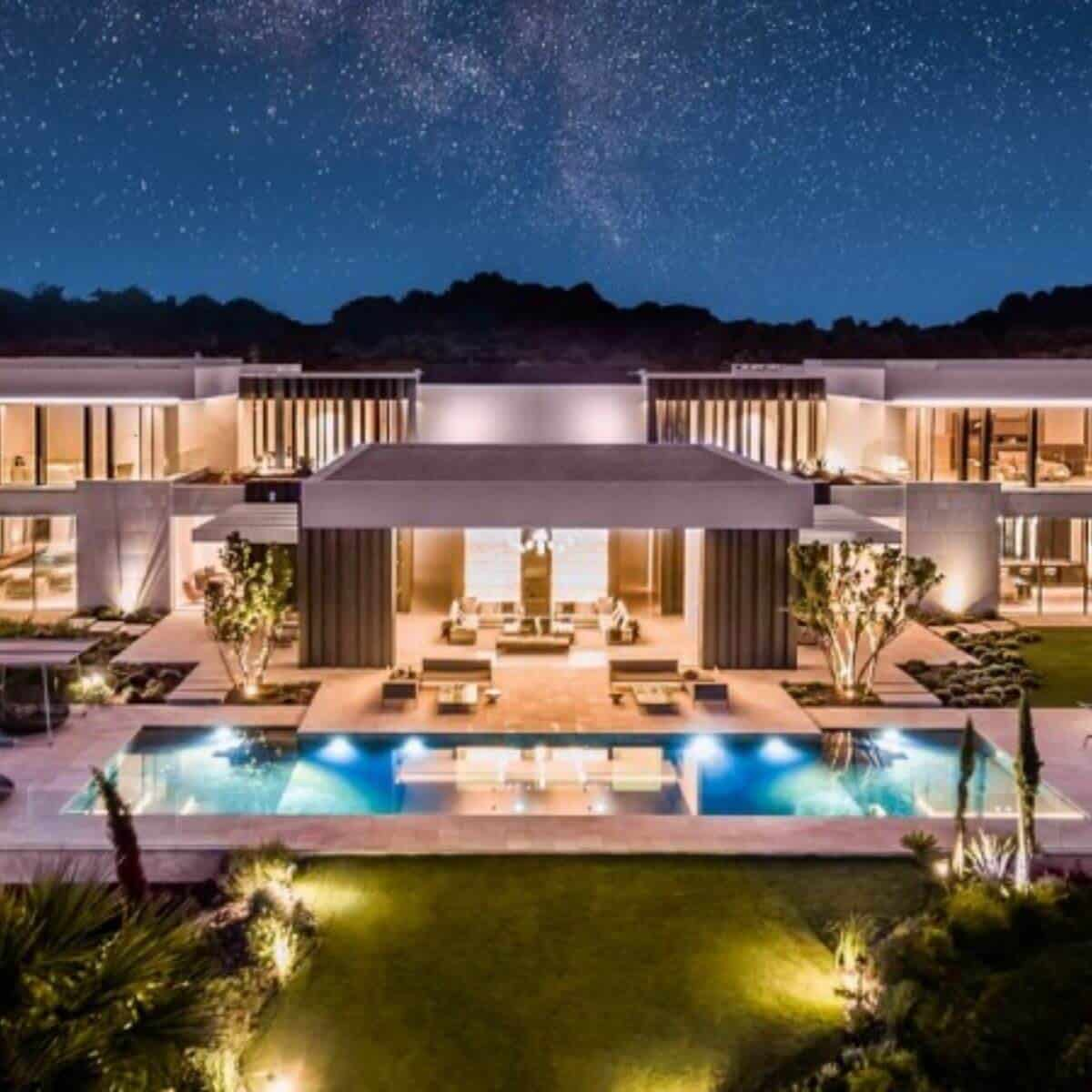 White and grey modern mansion in front of the mountains and stars.