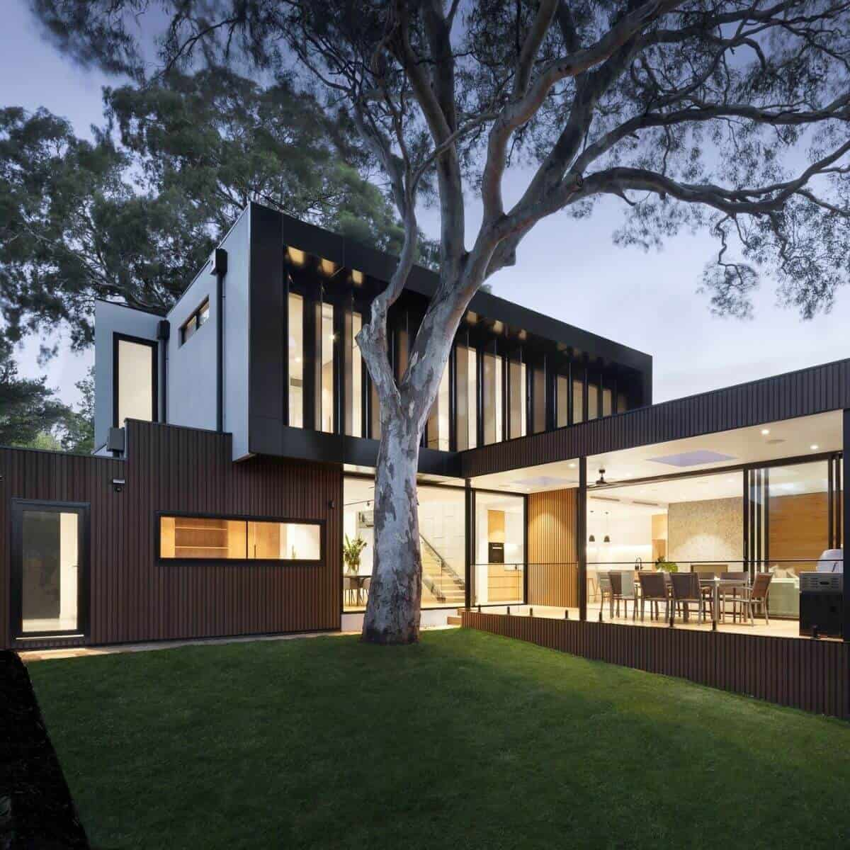 Black and wood modern mansion with a tree in front of it.