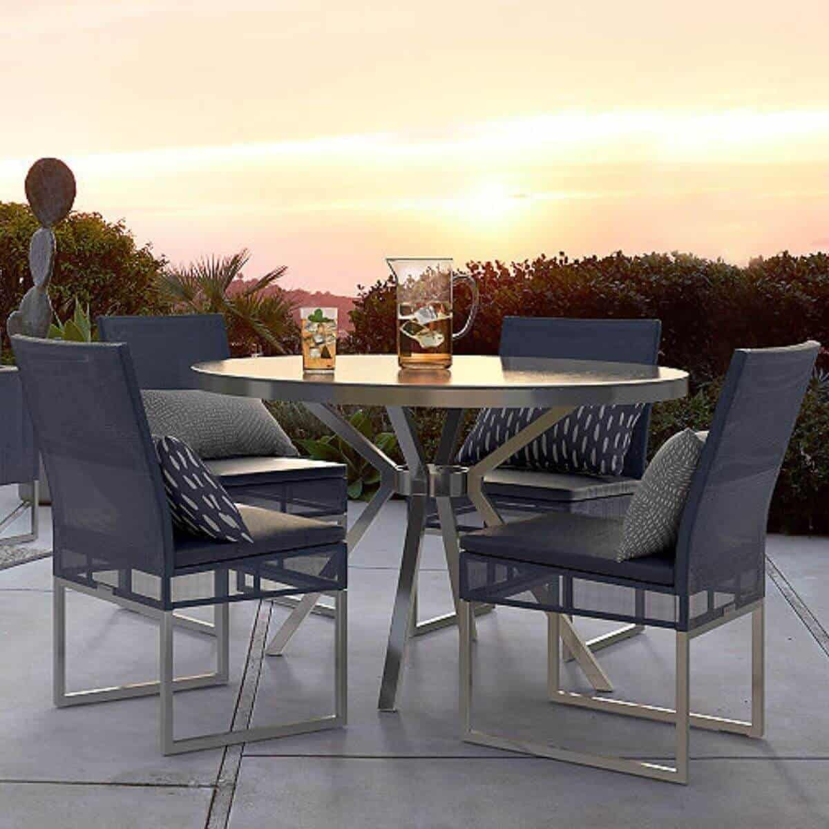 Outdoor dining table and chairs on a patio with a sunset.