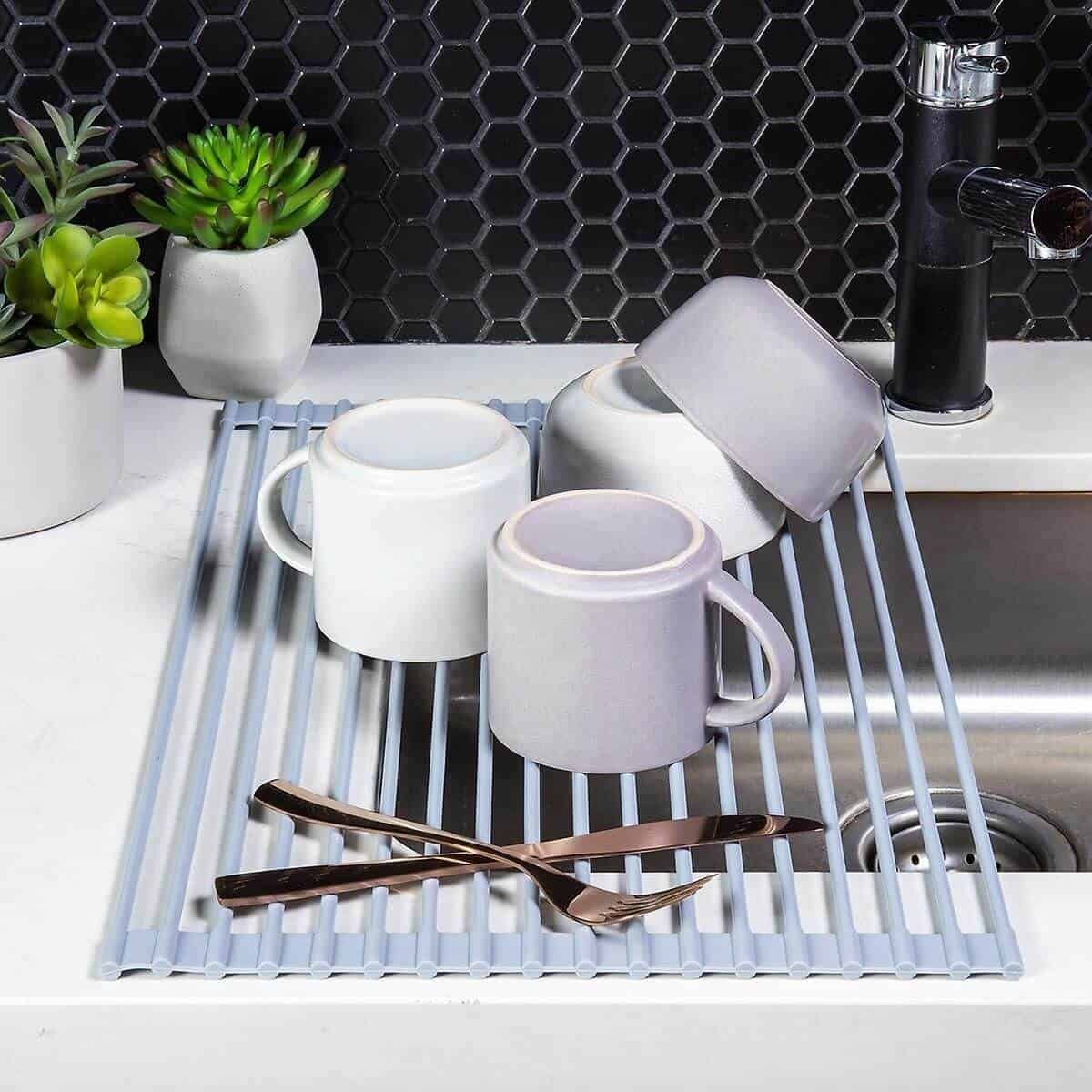 Roll-up drying rack on top of a sink with mugs, bowls, and tableware on it.