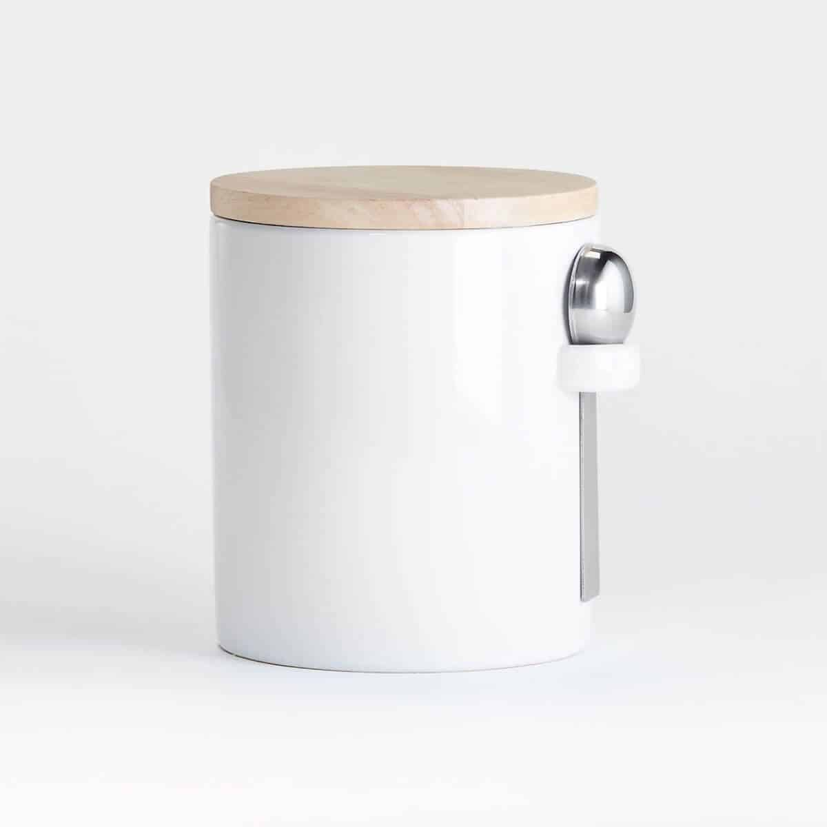 White canister with a spoon attached, and wooden lid.