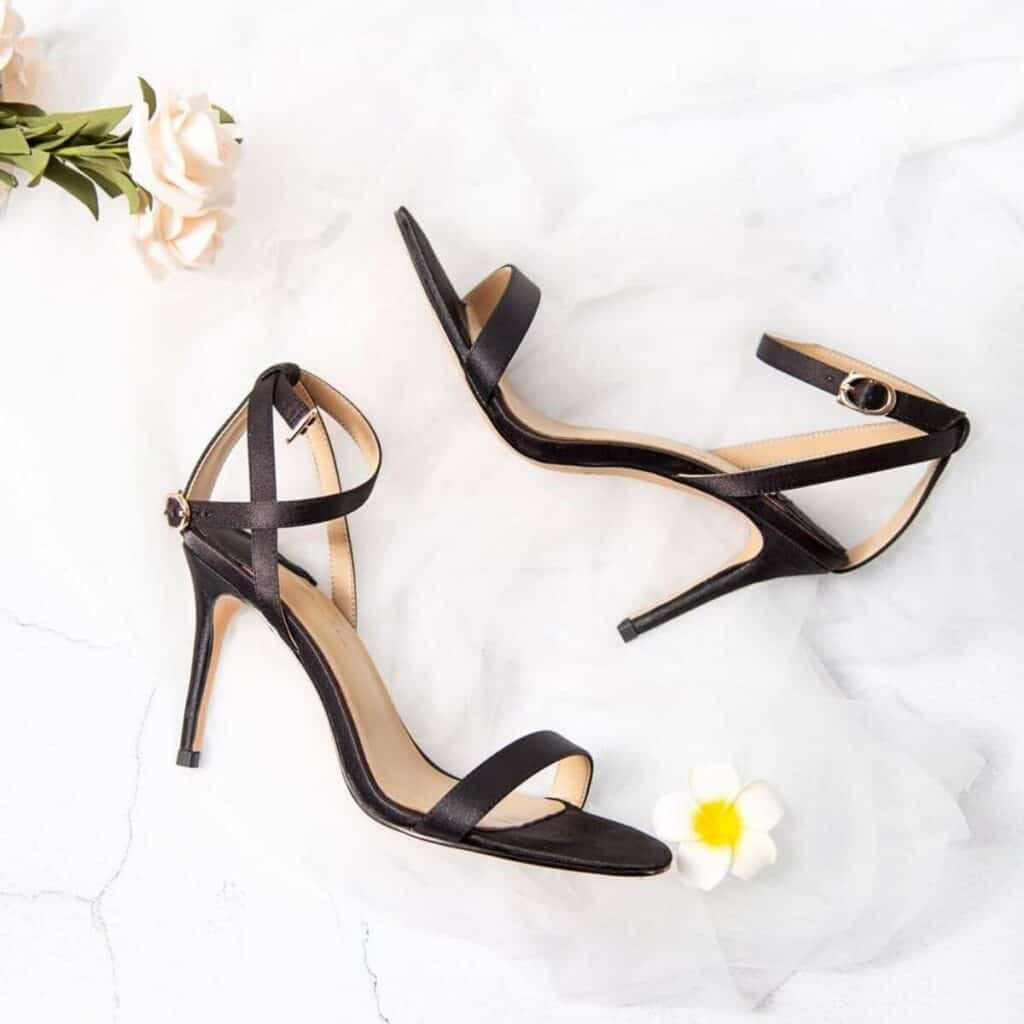 Black heels on a marble table with flowers.