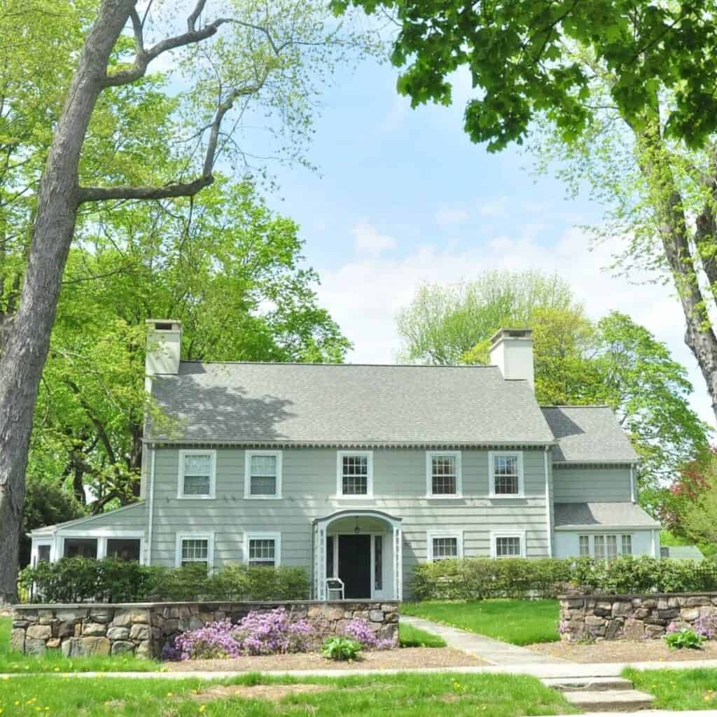 Light green Colonial-style house surrounded by trees.