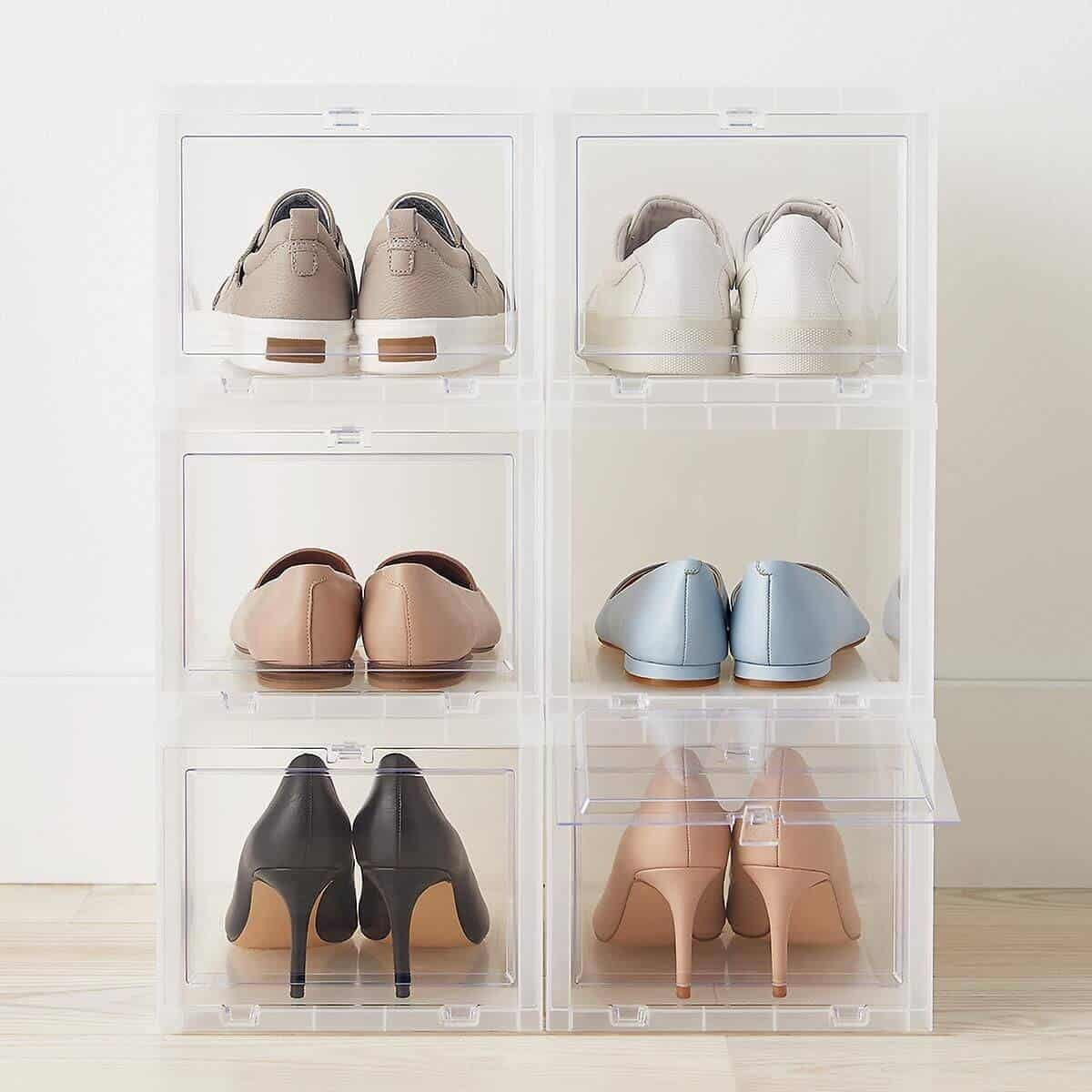 Two stacks of three clear shoe boxes with shoes in them.
