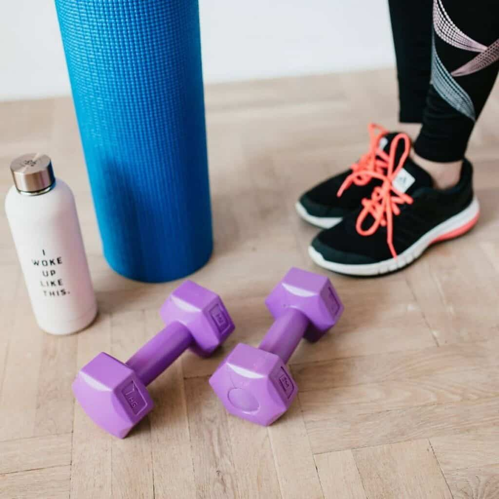 Weights, yoga mat, water bottle, and close-up of a person wearing running shoes.