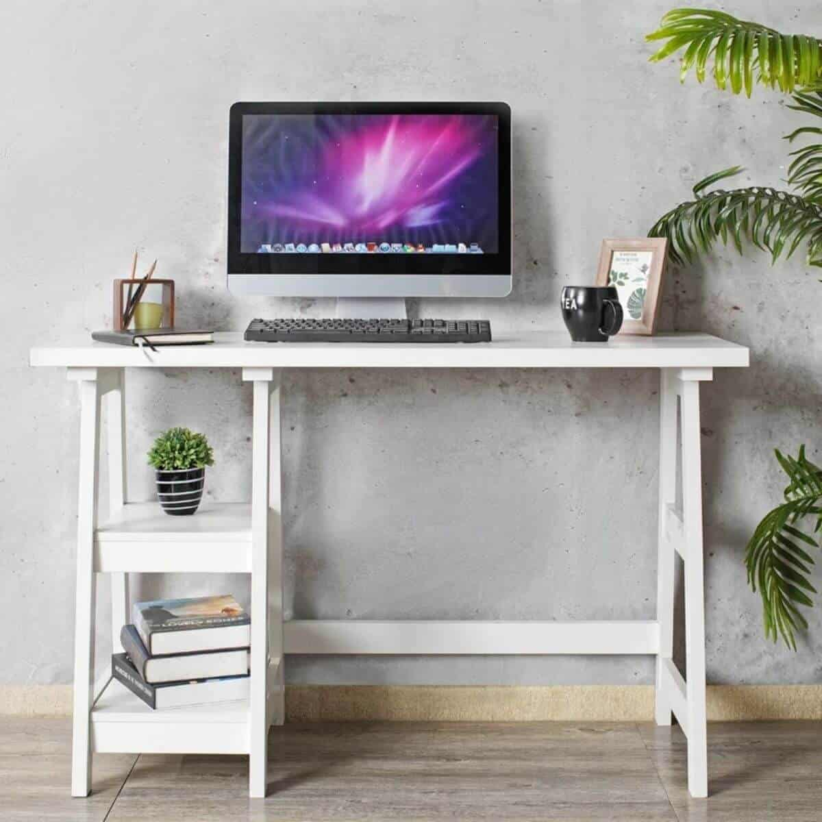 White desk against a cement wall with a computer and other office items on it.