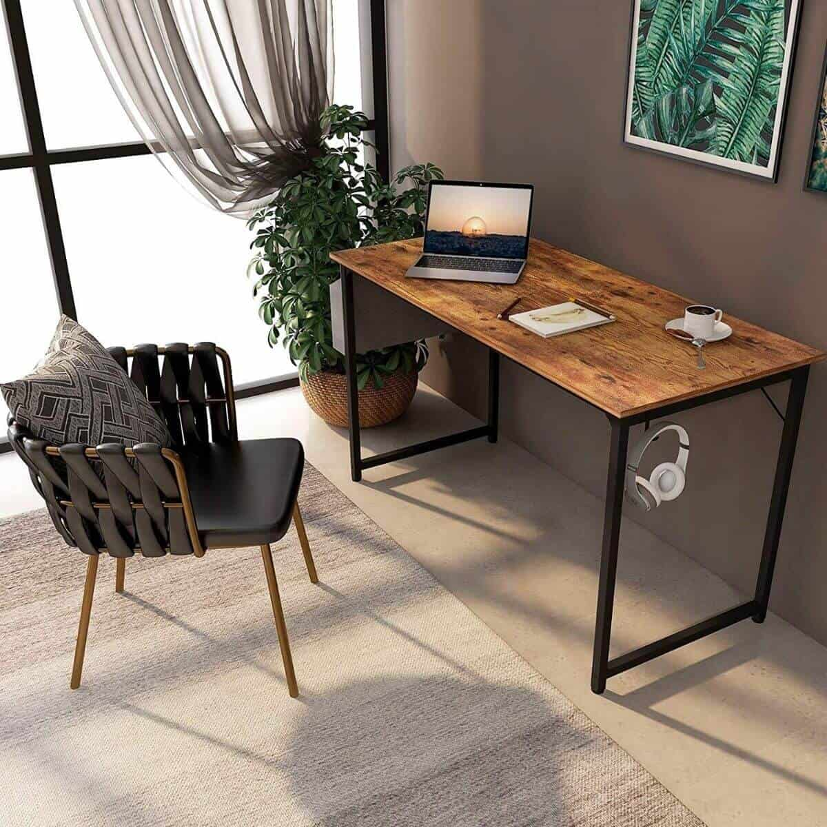 Room with a wooden desk, chair, rug, and plant.