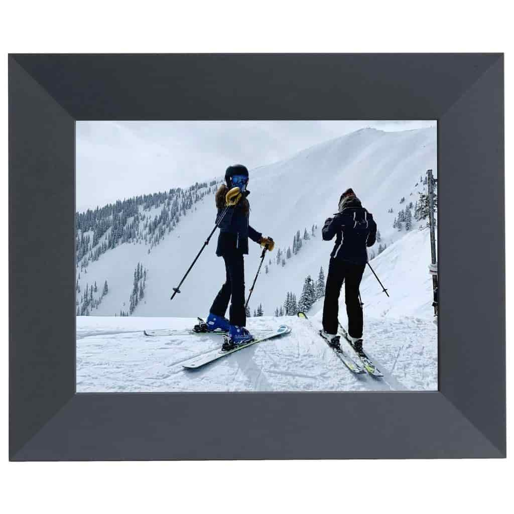 Black digital photo frame showing a photo of two people skiing.