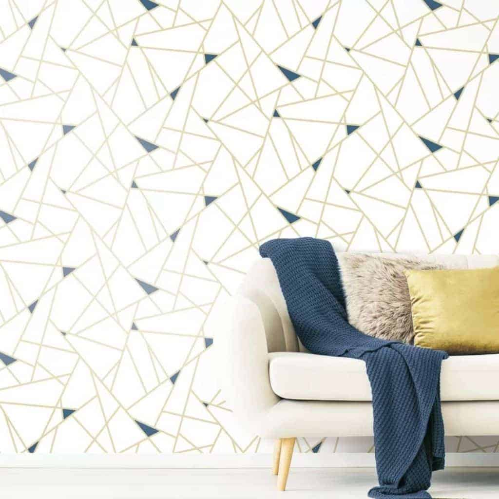 Gold and blue geometric shapes on wallpaper behind a couch.