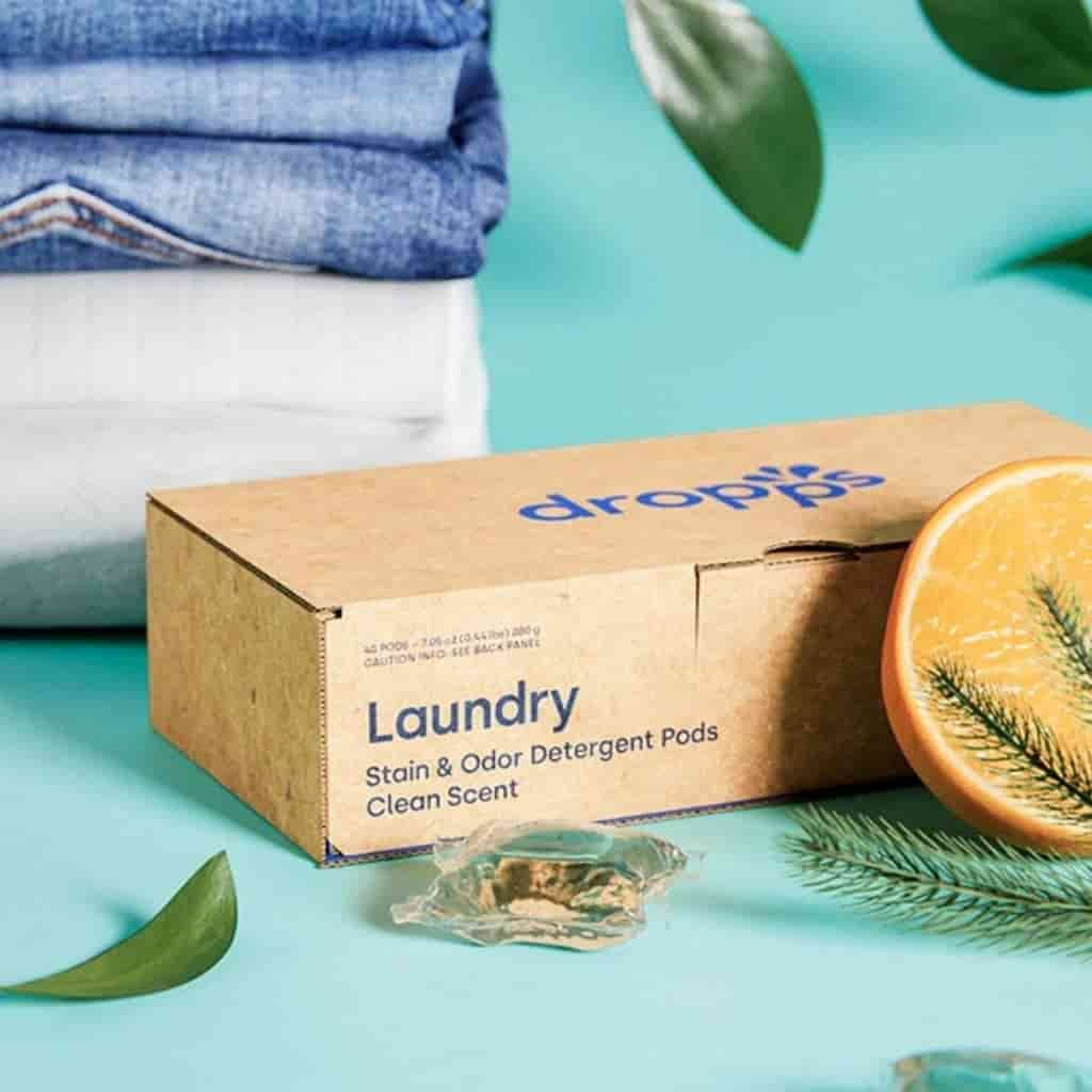 dropps laundry detergent box with leaves and folded clothes next to it.