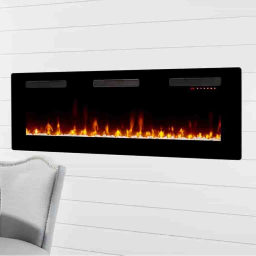 Electric fireplace mounted into a wall with a chair in front of it.