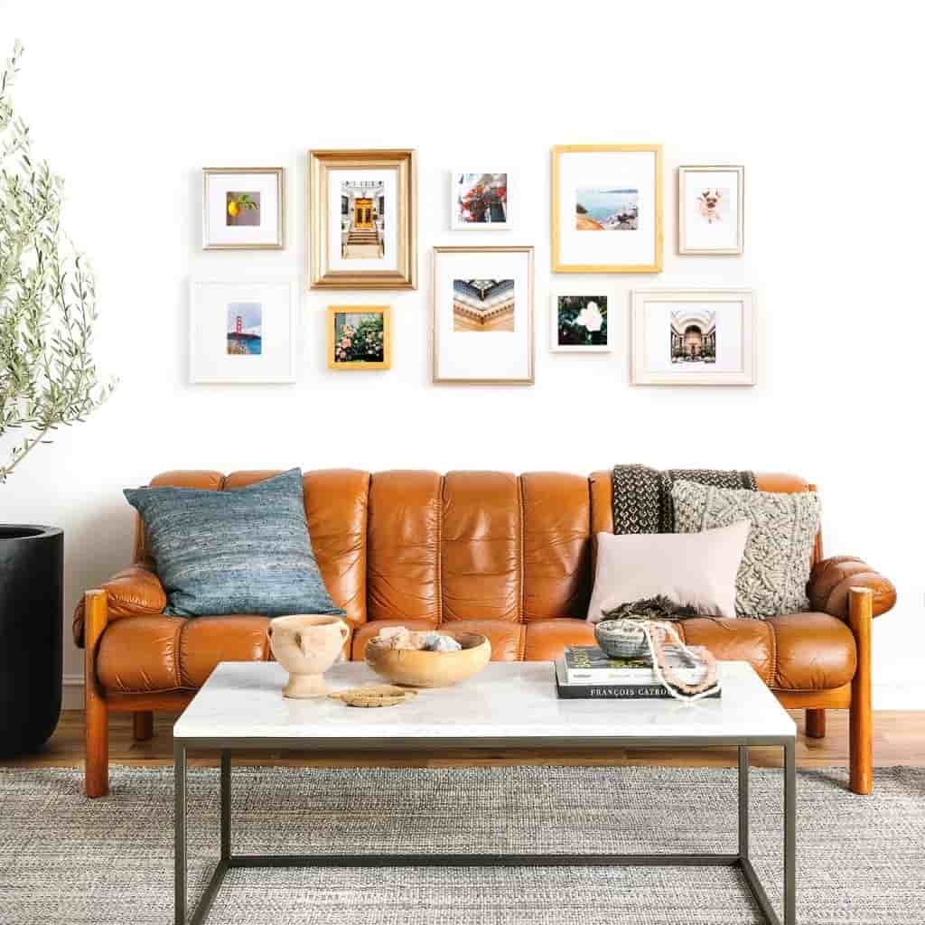 Gallery wall in a living room above a couch and table.