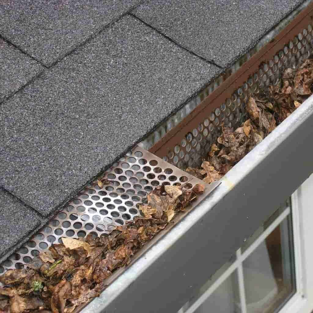 Metal gutter guards with dried leaves on it.
