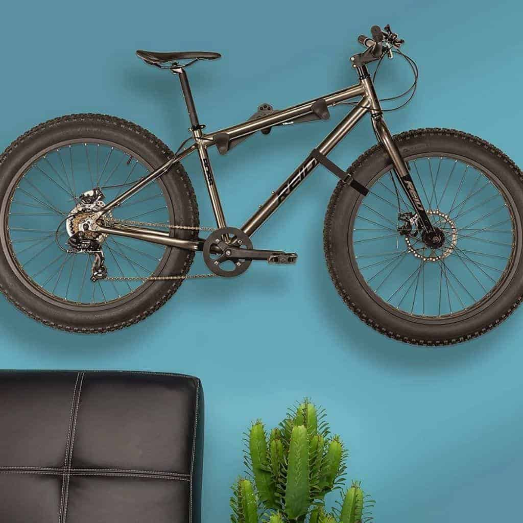 Bike mounted to a blue wall horizontally with a chair and plant underneath it.