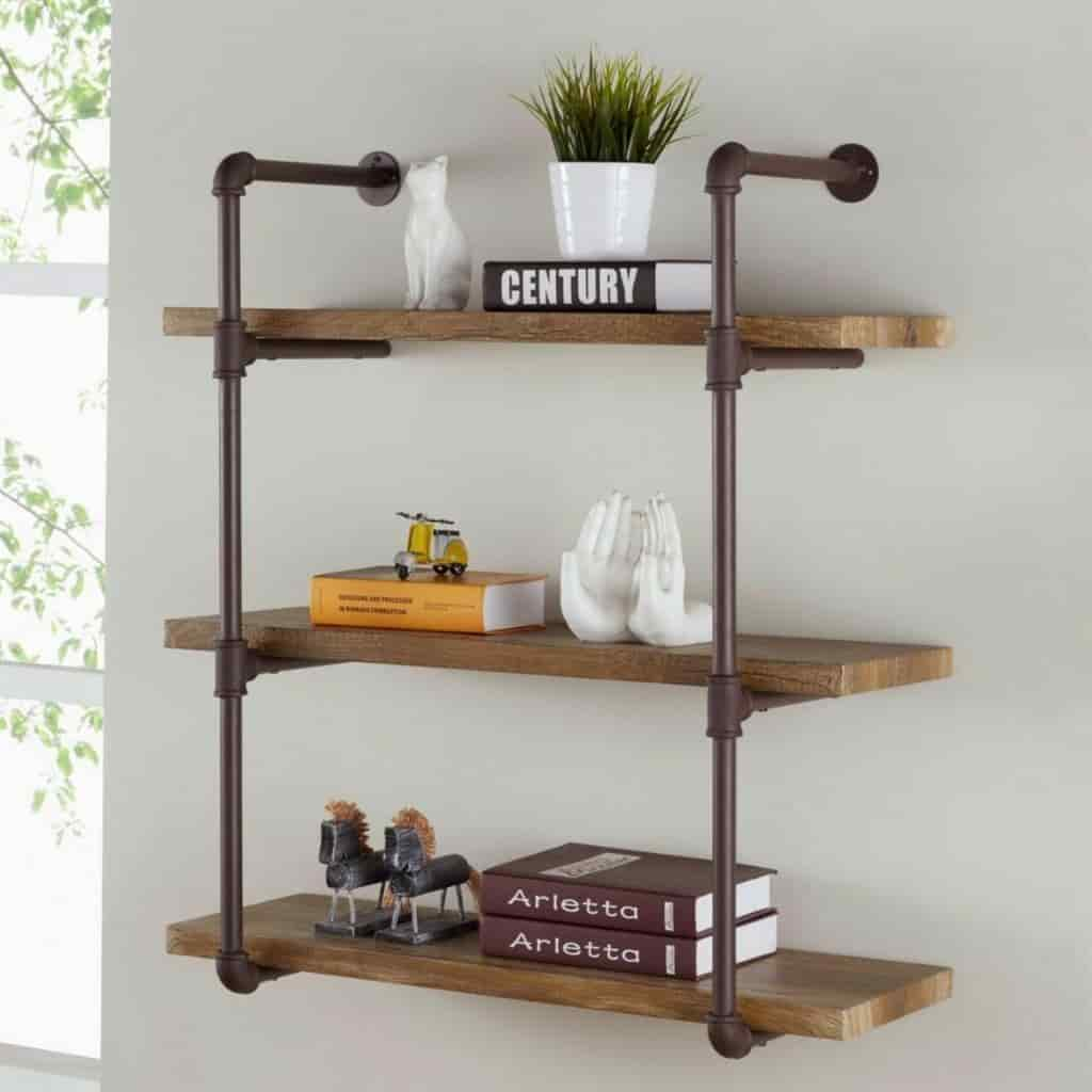 Industrial wooden wall shelves with books, a plant, and decor on it.