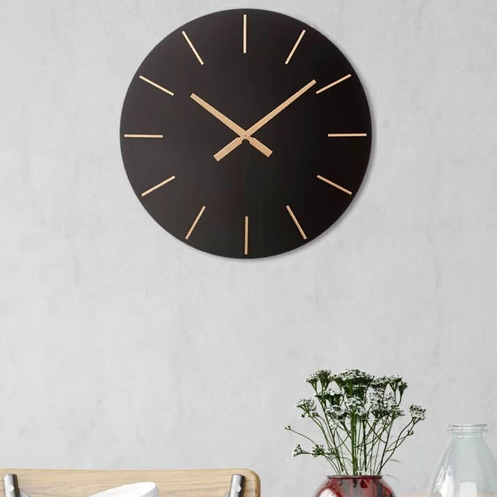 Black and gold oversized wall clock above a chair and plants.