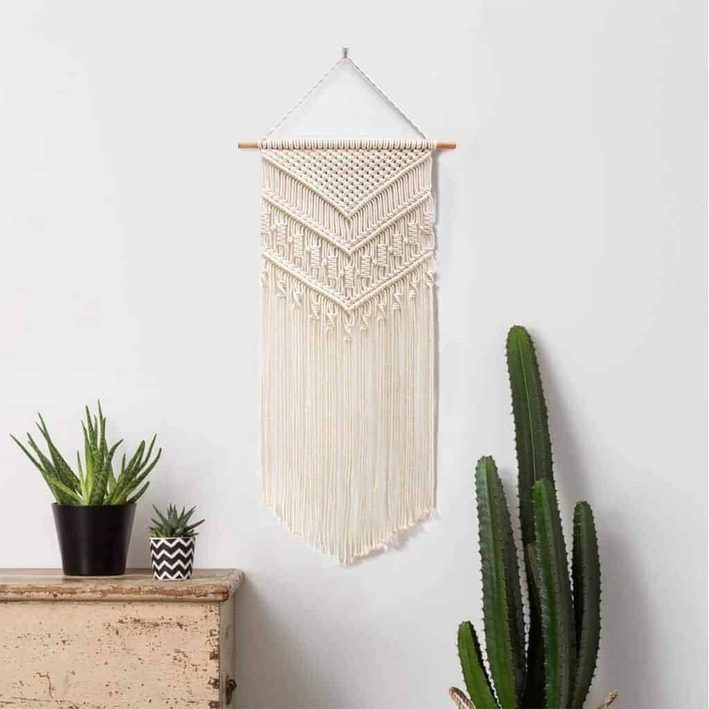 Macrame wall hanging above plants and a cabinet.