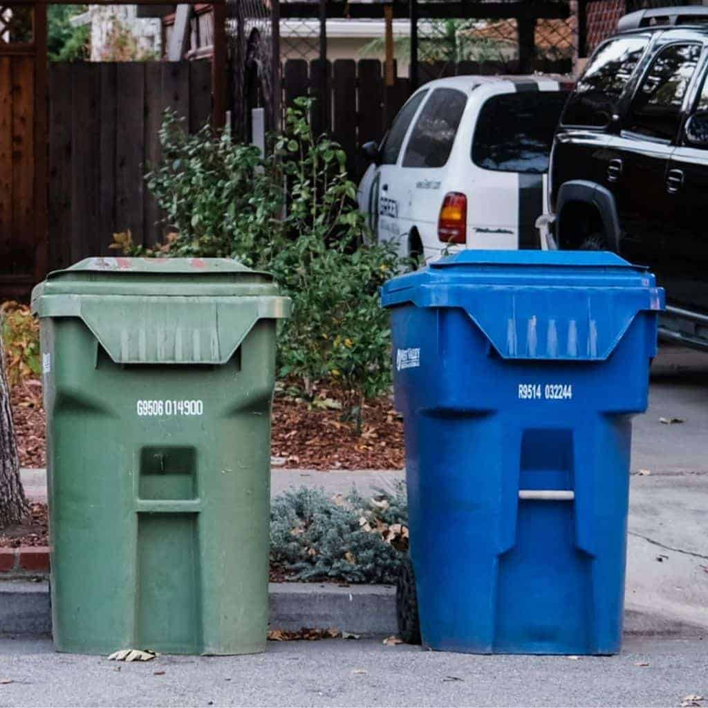 Trash and recycling bin in front of a house and cars.