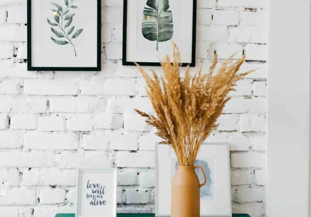 White brick wall with art and a green dresser in front of it with a plant on top.