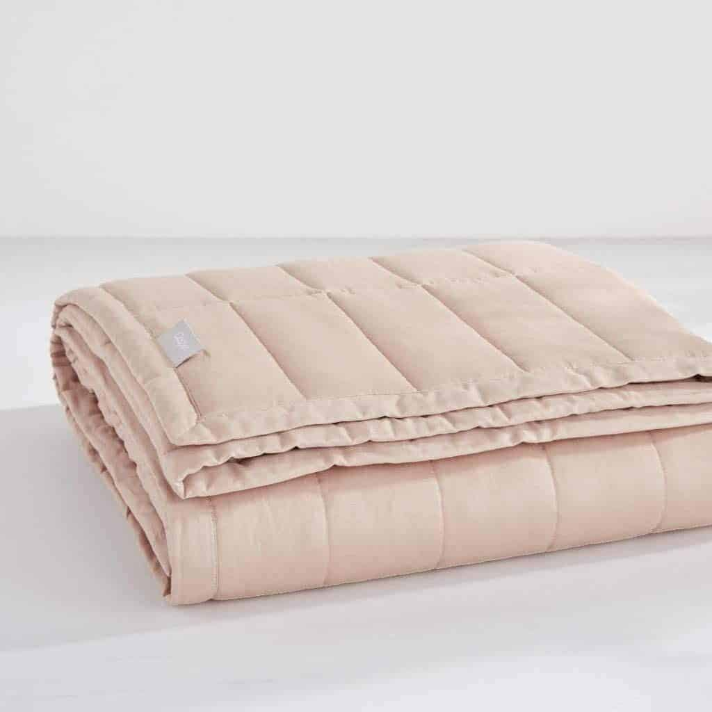 Rose-colored folded weighted blanket.