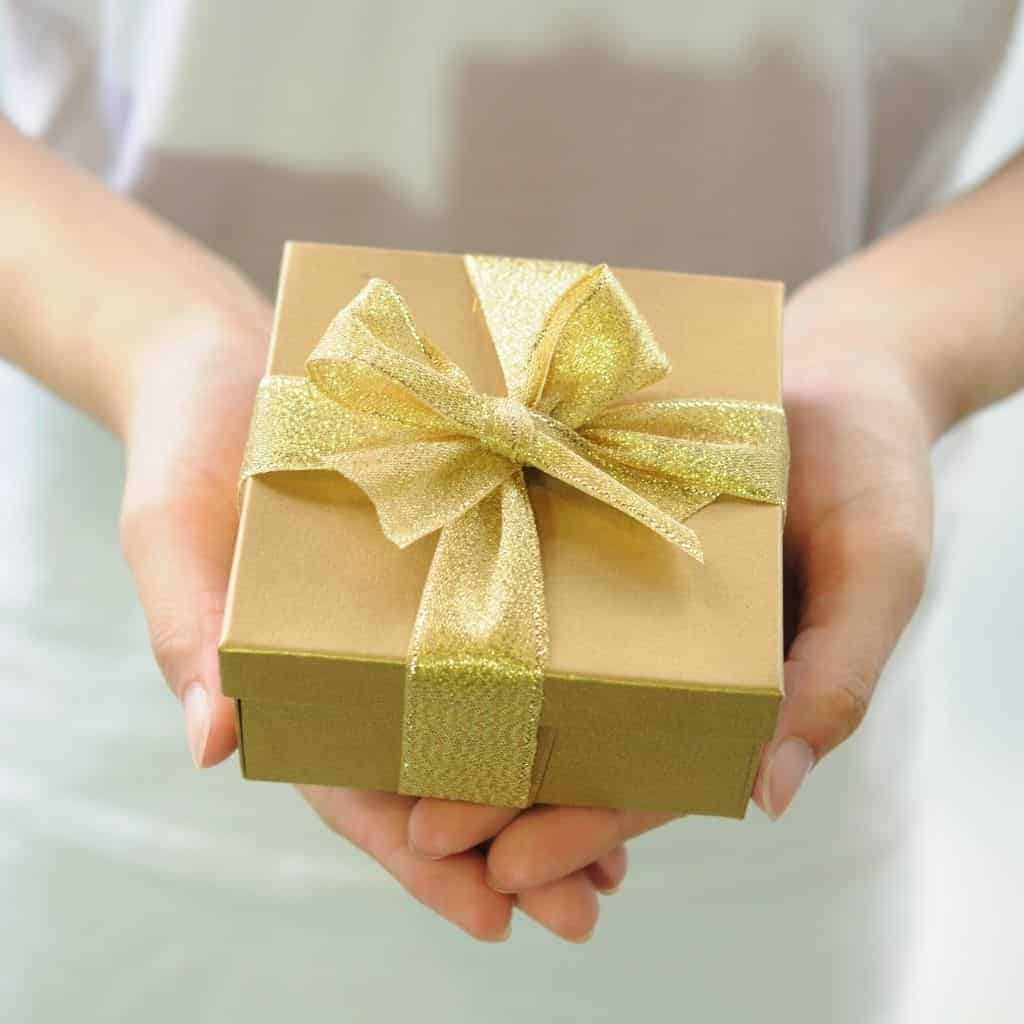 Person holding a gold present.