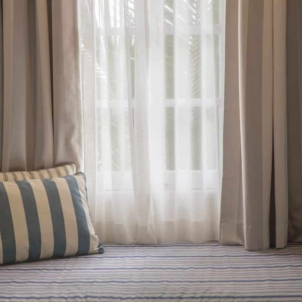 Pillows laying against grey and white curtains.