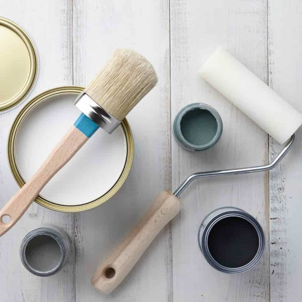 Paint brush and roller brush on cans.