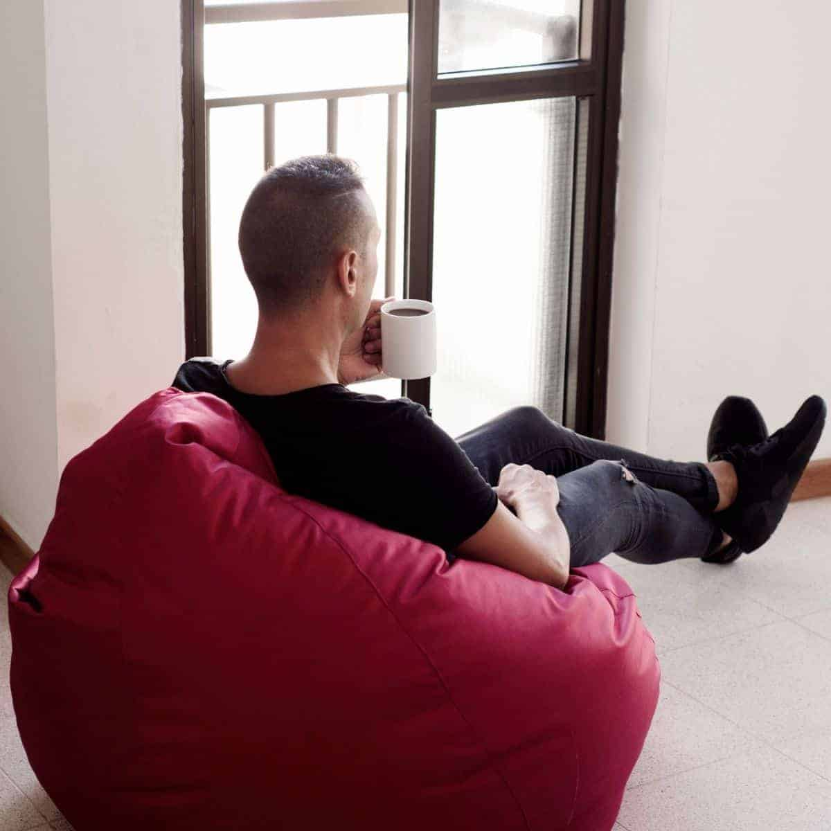 Person sitting in a bean bag chair and drinking coffee.