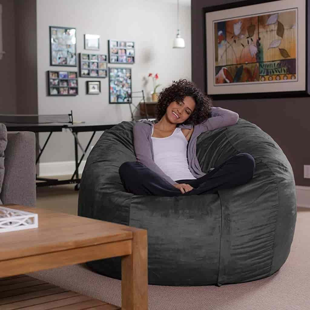 Person sitting on a Sofa Slack bean bag in a living room.
