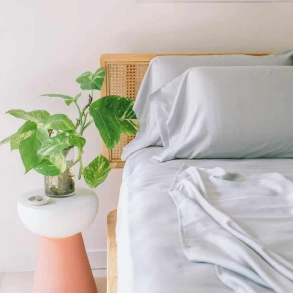 Grey bed sheets on a wooden bed with a plant next to it.