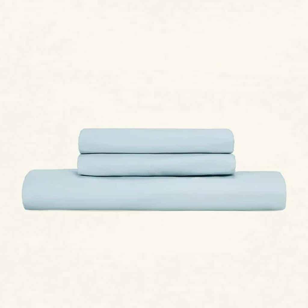 Stack of light blue bed sheets.