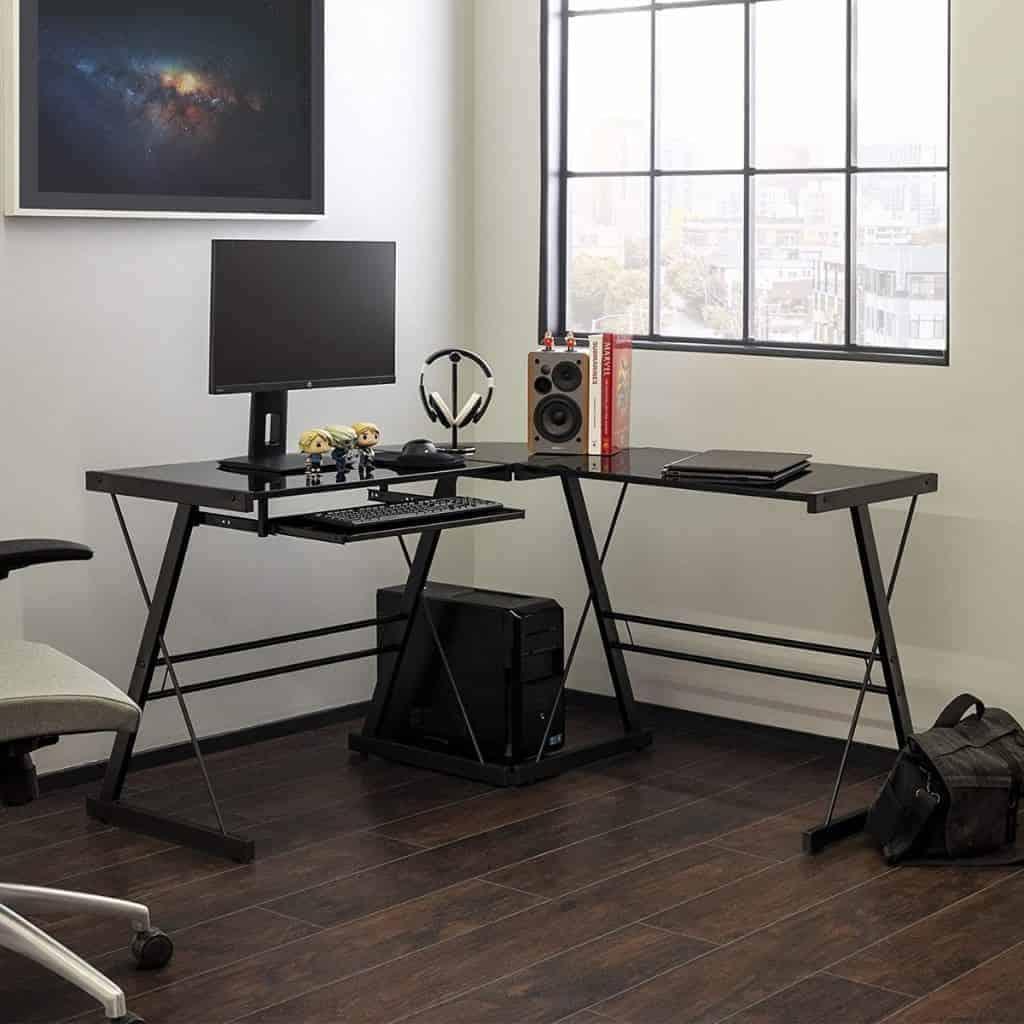 Black L-shaped desk in a room.