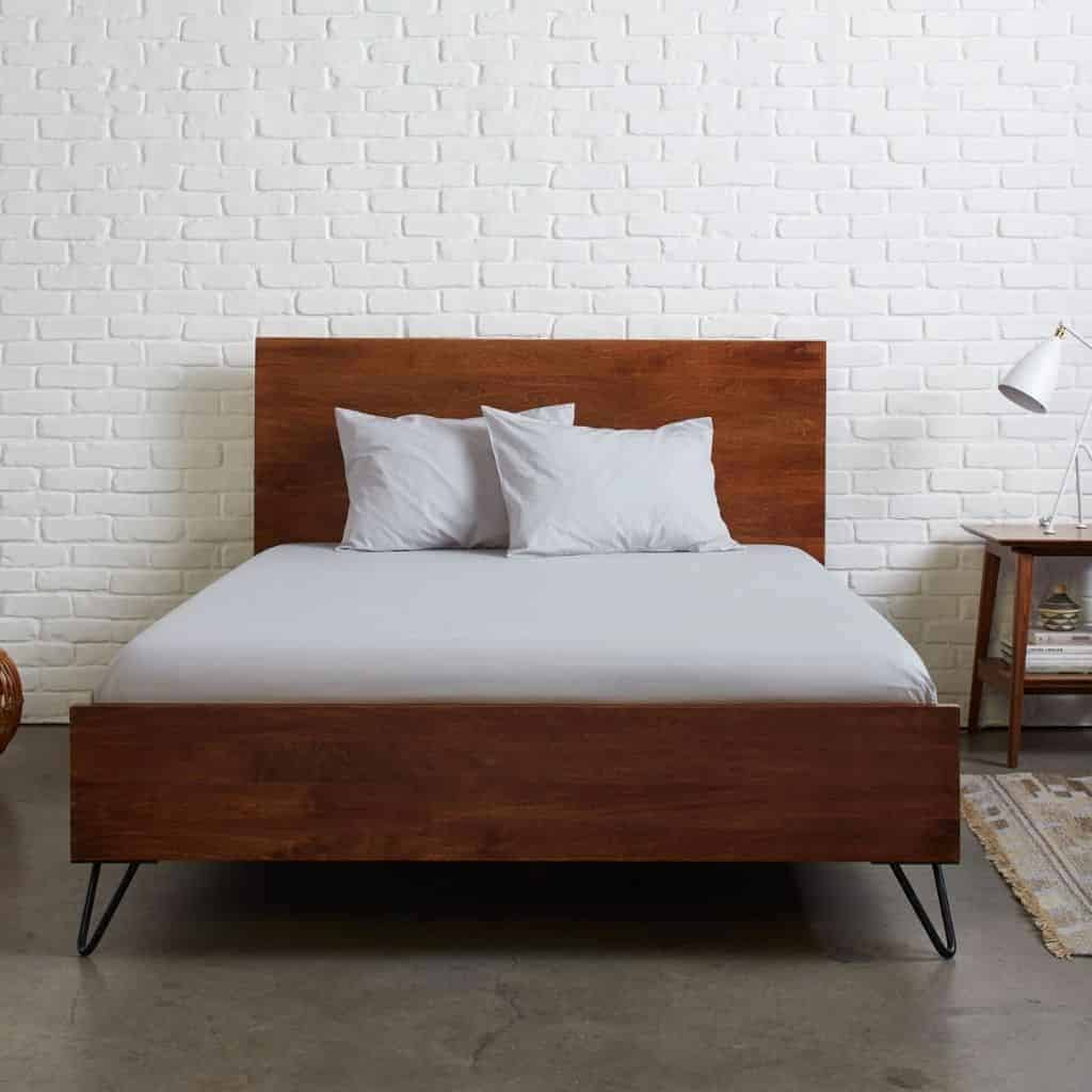Wooden bed frame with grey bed sheets.