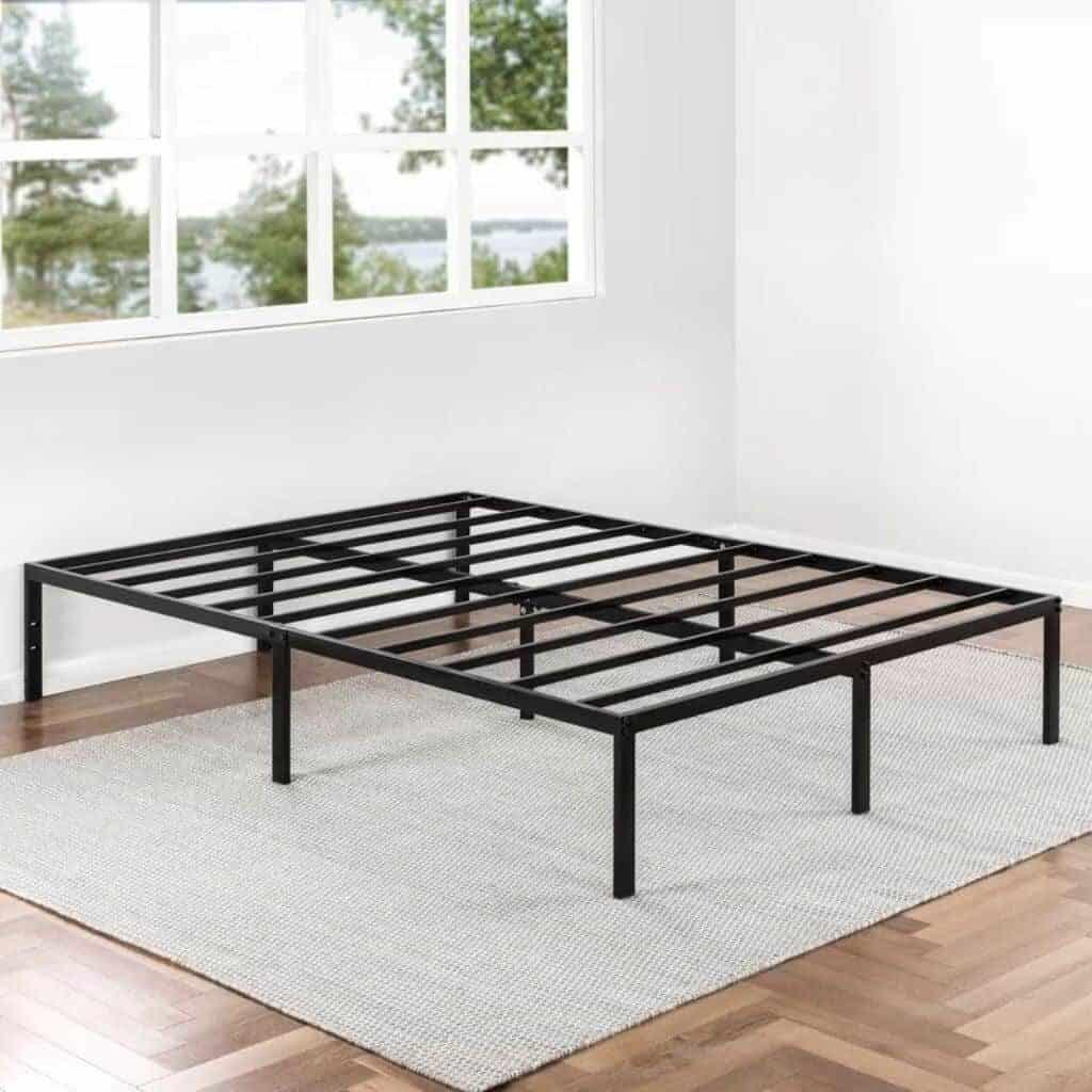 Black metal platform bed frame in an empty room.