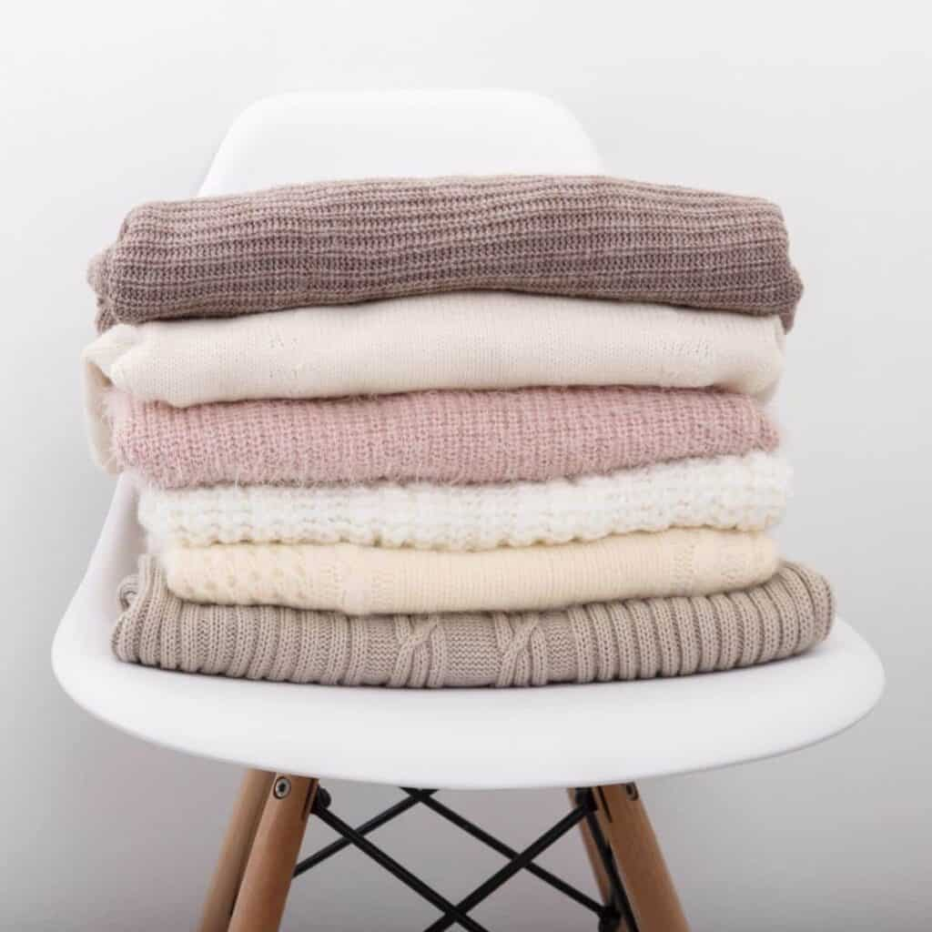 Stack of folded cashmere sweaters on a chair.