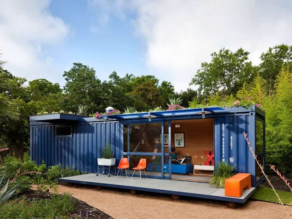 Container guest house surrounded by trees.
