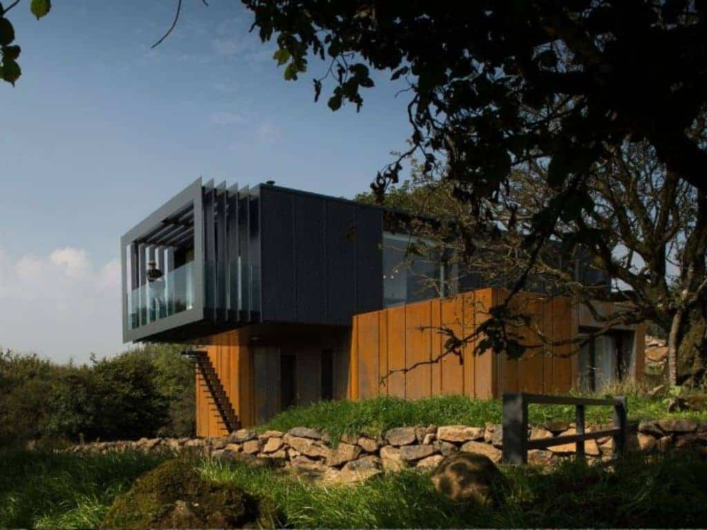 Exterior of a large shipping container home surrounded by trees.
