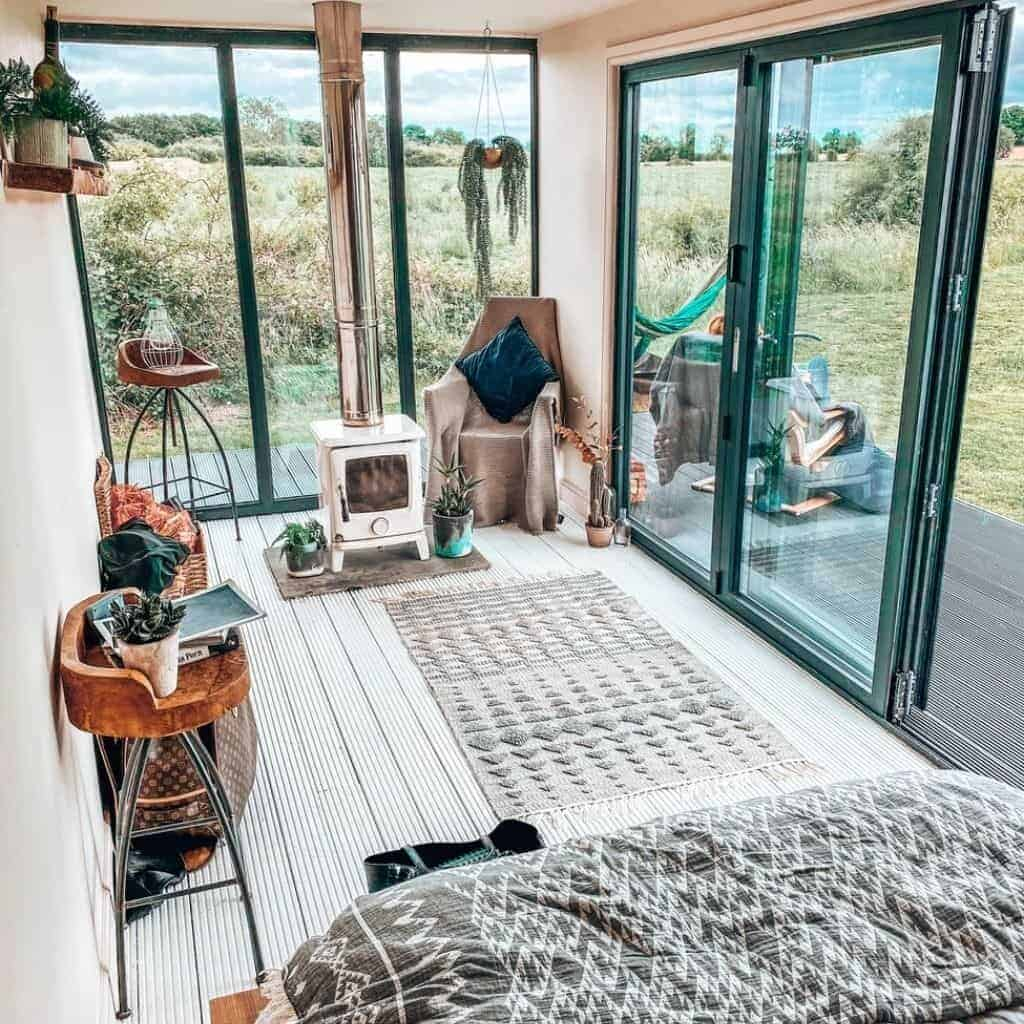 Interior of a tiny house with tall windows.