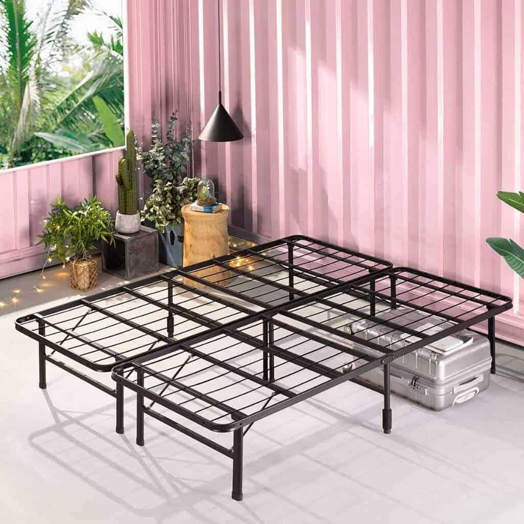 Metal platform bed frame in a pink room.