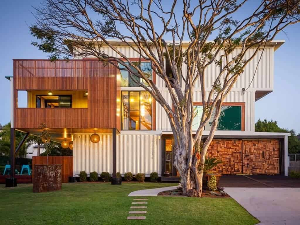 Three story container house with a tree in front of it.