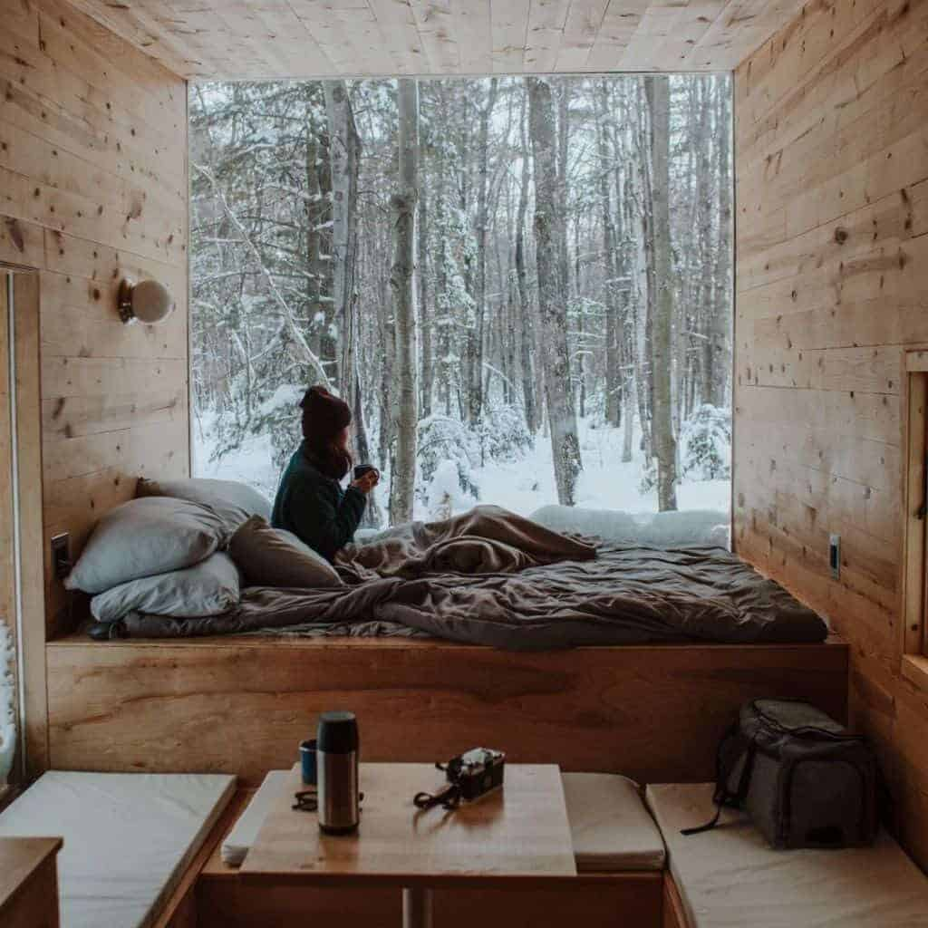 Inside a wooden tiny home in the snowy woods.